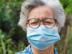 Portrait of an elderly woman wearing a face mask looking at the camera while standing in a garden. Mask for protect virus, coronavirus, pollen grains. Concept of old people and healthcare.