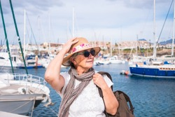 Portrait of an elderly woman with gray hairs and hat sitting at the port. A small port with yachts and sailboats. Cloudy and windy day