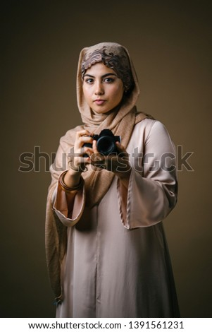 Portrait of an elegant and beautiful Middle Eastern Muslim woman in traditional and conservative brown dress and hijab head scarf smiles as she uses her DSLR camera in a studio.