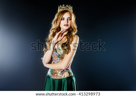 Portrait of an elegant girl blonde beauty queen in a smart green dress with a crown on the head of the winner