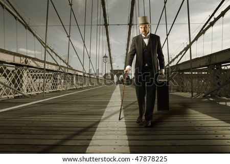 Portrait of an elegant man crossing a bridge with an old suitcase in his hand