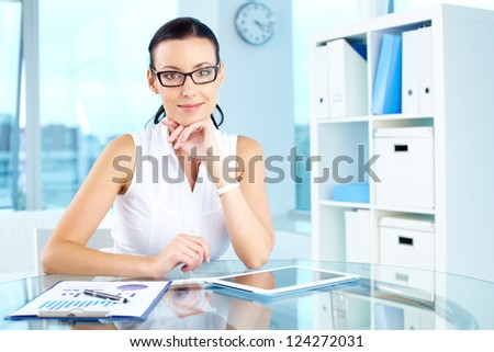 Portrait of an elegant manager sitting at her workplace