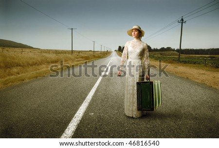 Portrait of an elegant woman standing on a countryside street with a suitcase in her hands