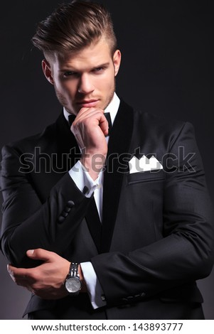 portrait of an elegant young fashion man in tuxedo looking at you with his hand at his chin and a pensive expression. on black background