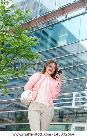 Portrait of an elegant young woman sending text message on mobile phone