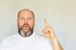 Portrait of an emotional man with a beard with a raised index finger against a white background.