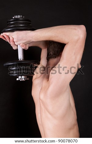 Portrait of an energetic naked man lifting dumbbell against black background