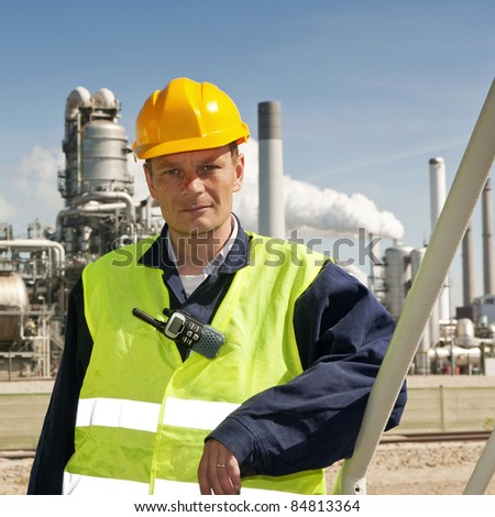 Portrait of an engineer in front of a petrochemical industry, with fire retardant clothing and a CB-radio clipped to a safety vest