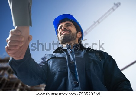 Portrait of an engineer shaking hands with a customer in front of a construction site