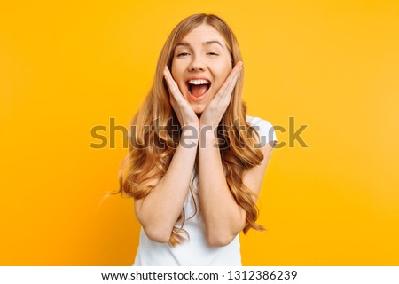 Portrait of an enthusiastic young girl screaming with joy over yellow background