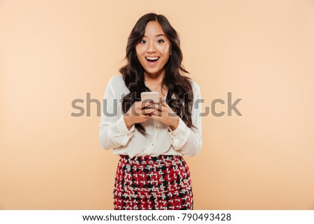Portrait of an excited asian woman standing and using mobile phone isolated over beige background #790493428