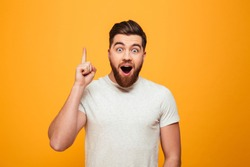 Portrait of an excited bearded man pointing finger up at copyspace isolated over yellow background
