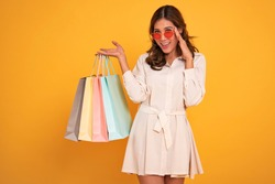 Portrait of an excited beautiful asian girl wearing dress and sunglasses holding shopping bags isolated on yellow background.