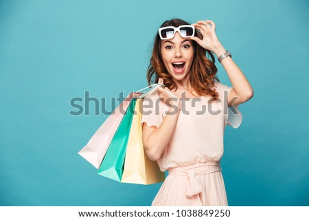 Portrait of an excited beautiful girl wearing dress and sunglasses holding shopping bags isolated over blue background #1038849250