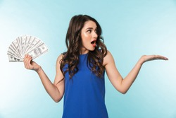 Portrait of an excited beautiful young brunette woman standing isolated over blue background, showing money banknotes