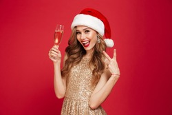 Portrait of an excited cheerful woman in christmas hat and dress holding champagne glass while standing and showing peace gesture isolated over red background