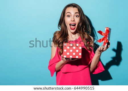 Portrait of an excited cute girl in dress holding opened present box isolated over blue background #644990515
