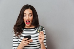 Portrait of an excited girl looking at mobile phone while standing and holding credit card isolated over gray background