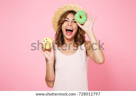 Portrait of an excited happy woman in summer hat holding donuts isolated over pink background #728012797
