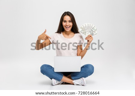Portrait of an excited satisfied asian girl holding money banknotes while sitting with laptop computer on her lap and pointing finger isolated over white background