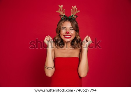 Portrait of an excited smiling girl wearing christmas deer costume while standing with eyes closed isolated over red background
