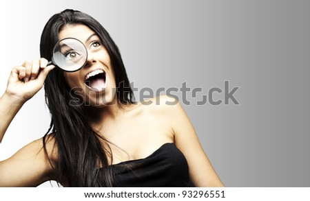 portrait of an excited woman looking through a magnifying glass over a grey background
