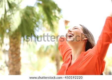 Portrait of an excited woman with eyes closed raising arms skyward outdoors with palm trees in the background