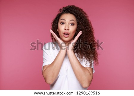 Portrait of an excited young african woman screaming isolated over pink background #1290169516