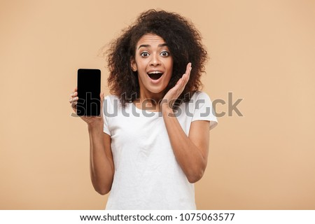 Portrait of an excited young african woman showing blank screen mobile phone isolated over beige background