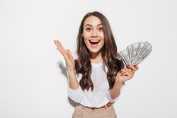 Portrait of an excited young asian businesswoman showing money banknotes and celebrating isolated over white background
