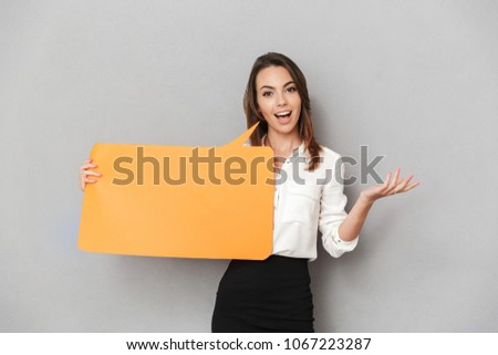 Portrait of an excited young business woman holding empty speech bubble isolated over white background
