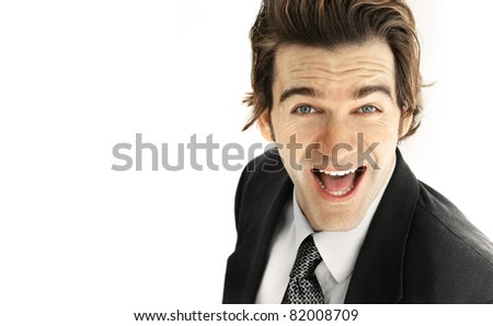 Portrait of an excited young businessman with big smile against neutral white background - stock photo