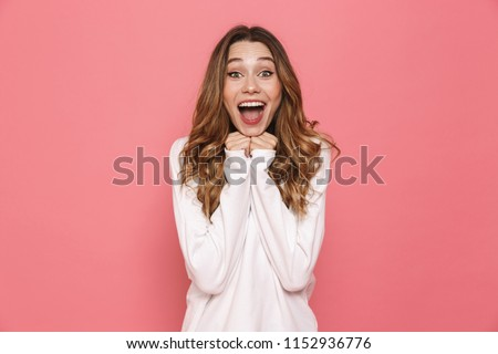Portrait of an excited young casual girl screaming isolated over pink background #1152936776