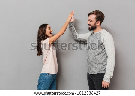 Portrait of an excited young couple giving high five over gray background #1012536427