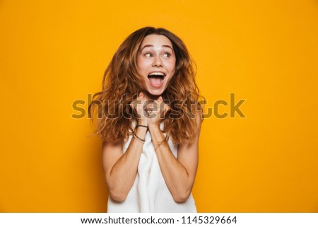 Portrait of an excited young girl screaming isolated over yellow background #1145329664