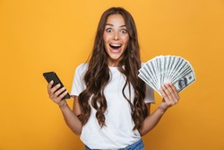 Portrait of an excited young girl with long brunette hair standing over yellow background, holding money banknotes, using mobile phone