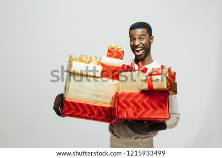 Portrait of an excited  young man holding many gifts, isolated on white studio background