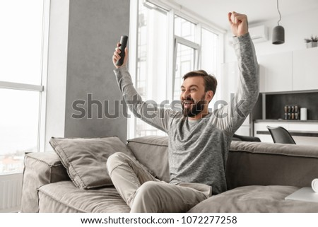 Portrait of an excited young man holding TV remote control while sitting on a couch at home and celebrating