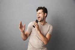 Portrait of an excited young man in t-shirt isolated over gray backgound, holding blank screen mobile phone, singing