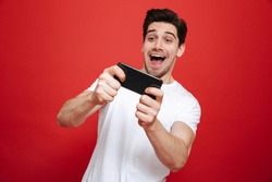 Portrait of an excited young man in white t-shirt playing games on mobile phone isolated over red background
