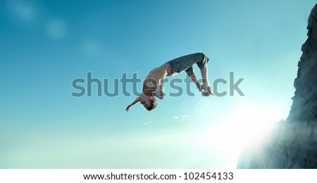 Portrait of an excited young man jumping in air against blue sky #102454133