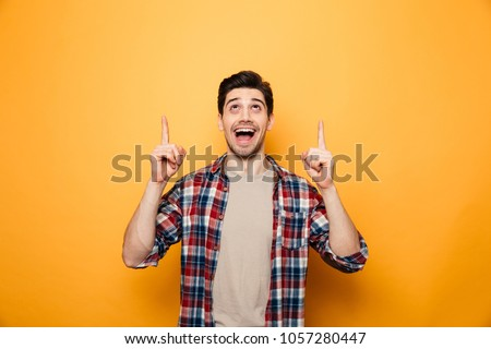 Portrait of an excited young man pointing fingers up at copy space isolated over yellow background #1057280447