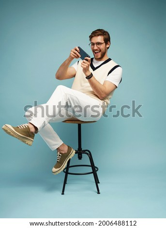 Portrait of an excited young man sitting on a stool and playing games on mobile phone isolated over blue background.