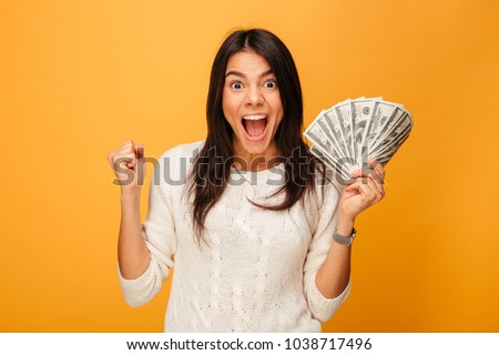 Portrait of an excited young woman holding money banknotes and celebrating isolated over yellow background