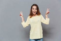 Portrait of an excited young woman in sweater showing peace signs with hands isolated on the gray background