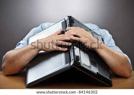 Portrait of an exhausted businessman covering his head with his laptop - stock photo
