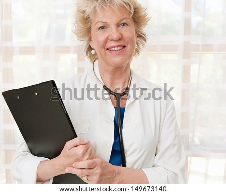 Portrait of an experienced and mature female doctor standing in a hospital room with a clipboard folder and a stethoscope around her neck, during a day at work.