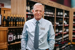 Portrait of an expert sommelier standing in wine store. Supermarket liquor section manager looking at camera.