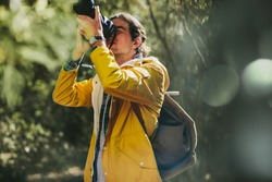 Portrait of an explorer taking photos of nature standing in a forest. Photographer wearing jacket and backpack doing nature photography.