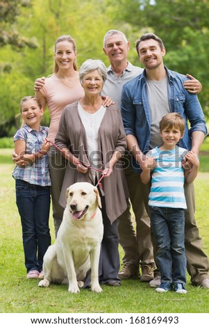 Portrait of an extended family with their pet dog standing at the park